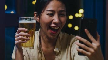 jeune femme asiatique buvant de la bière s'amusant moment heureux fête du nouvel an événement en ligne célébration par appel vidéo par téléphone à la maison la nuit. distanciation sociale, quarantaine pour la prévention des coronavirus. photo