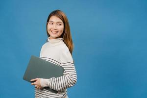 une jeune femme asiatique tient un ordinateur portable avec une expression positive, sourit largement, vêtue de vêtements décontractés, se sentant heureuse et se tient isolée sur fond bleu. heureuse adorable femme heureuse se réjouit du succès. photo