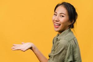 portrait d'une jeune femme asiatique souriante avec une expression joyeuse, montre quelque chose d'étonnant dans un espace vide dans un tissu décontracté et regardant la caméra isolée sur fond jaune. concept d'expression faciale. photo
