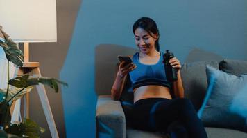 jeune femme asiatique utilisant un téléphone portable et buvant de l'eau pure sur un canapé dans le salon la nuit à la maison. activité sportive et récréative, distanciation sociale, quarantaine pour le concept de prévention du virus corona. photo