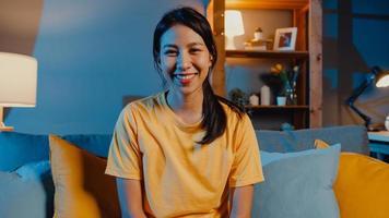 heureuse jeune femme asiatique indépendante regardant la caméra sourire et parler avec un ami lors d'un appel vidéo en ligne la nuit dans le salon à la maison, rester à la maison en quarantaine, travailler à domicile, concept de distanciation sociale. photo
