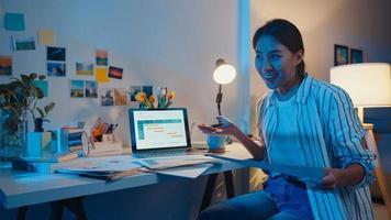 jeune femme d'affaires asiatique prépare la présentation avant l'entretien de la conférence au bureau à domicile. travail de la maison surchargée la nuit, à distance, distanciation sociale, quarantaine pour la prévention du virus corona. photo