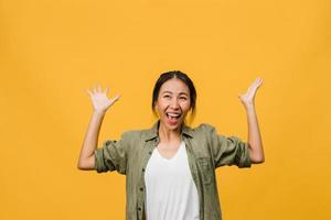 portrait d'une jeune femme asiatique avec une expression positive, un large sourire, vêtue de vêtements décontractés sur fond jaune. heureuse adorable femme heureuse se réjouit du succès. concept d'expression faciale. photo