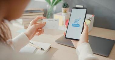 gros plan jeune femme asiatique utilise un téléphone portable pour commander des produits d'achat en ligne et paie des factures avec une carte de crédit à l'intérieur du salon à la maison, activité d'auto-quarantaine, activité amusante pour la prévention des coronavirus. photo