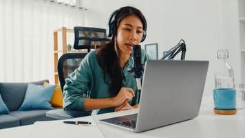 une fille asiatique heureuse enregistre un podcast sur son ordinateur portable avec des écouteurs et un microphone parle avec le public dans sa chambre. une podcasteuse crée un podcast audio depuis son home studio, reste à la maison concept. photo