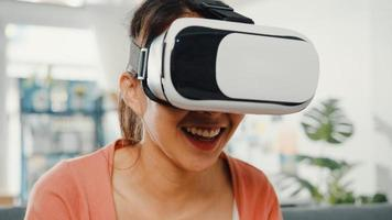 dame asiatique portant des lunettes de casque de réalité virtuelle gesticulant la main assise sur un canapé dans le salon de la maison. rester à la maison en quarantaine covid, ré-imaginer la réalité, technologie vr du futur concept. photo