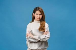 jeune femme asiatique avec une expression négative, criant excité, pleurant émotionnellement en colère dans des vêtements décontractés et regardant la caméra isolée sur fond bleu. heureuse adorable femme heureuse se réjouit du succès. photo