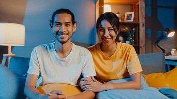 heureux jeune couple asiatique homme et femme regardant la caméra sourire et joyeux lors d'un appel vidéo en ligne la nuit dans le salon à la maison, rester à la maison en quarantaine, vie conjugale, concept de distanciation sociale. photo