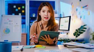 femme d'affaires asiatique distanciation sociale dans une nouvelle norme pour la prévention des virus en regardant la présentation de la caméra à un collègue au sujet du plan en appel vidéo pendant le travail de nuit au bureau. mode de vie après le coronavirus. photo