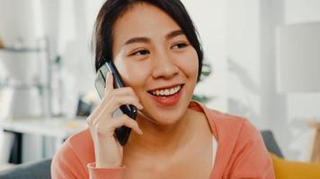 belle dame d'asie assise sur un canapé appel téléphonique avec un ami à la maison. rester à la maison, relation longue distance, relation familiale, garder la distance, concept de quarantaine covid. photo