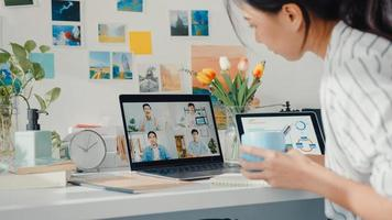 une jeune employée asiatique écoute le leader lors d'un appel vidéo avec divers collègues multiraciaux en ligne avec un ordinateur portable à la maison. Apprentissage à distance. étudiante apprend en ligne à la maison, concept de réunion en ligne. photo