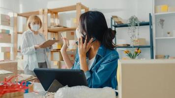 les jeunes femmes d'affaires asiatiques portent un masque facial à l'aide d'un appel téléphonique recevant la commande d'achat et vérifient le produit en stock au bureau à domicile. propriétaire de petite entreprise, concept indépendant de livraison de marché en ligne. photo