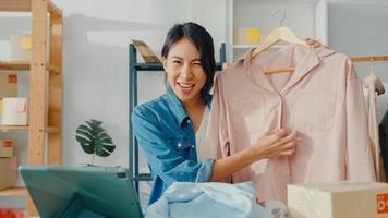 jeune créatrice de mode asiatique utilisant un téléphone portable recevant un bon de commande et montrant des vêtements enregistrant une vidéo en direct en ligne dans la boutique. propriétaire de petite entreprise, concept de livraison de marché en ligne. photo
