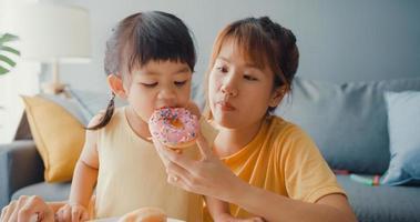 Joyeuse famille asiatique joyeuse maman et petite fille mangeant des beignets et s'amusant se détendre profiter du canapé dans le salon de la maison. passer du temps ensemble, distance sociale, quarantaine pour le coronavirus. photo