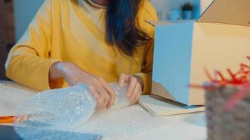 jeune femme d'affaires asiatique emballage verre utiliser du papier bulle pour le support d'emballage endommager le produit fragile dans le bureau à domicile la nuit. propriétaire de petite entreprise, livraison sur le marché en ligne, concept de style de vie indépendant. photo
