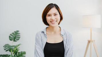 portrait de belle femme d'affaires exécutive vêtements décontractés intelligents regardant la caméra et souriant, heureux dans un lieu de travail de bureau moderne. une jeune femme asiatique parle à un collègue lors d'une réunion par appel vidéo à la maison. photo