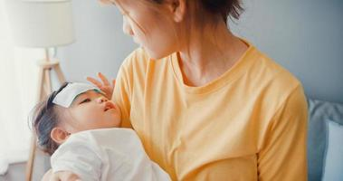 Joyeuse mère de famille asiatique joyeuse tenant une petite fille malade dans les bras et attachez le gel antipyrétique sur le front de bébé marchez dans le salon de la maison. assurance soins médicaux, traitement et concept de soins de santé. photo