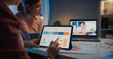 des femmes d'affaires asiatiques utilisant un ordinateur portable parlent à leurs collègues du plan lors d'une réunion par appel vidéo au bureau à domicile. travailler à partir de la surcharge de la maison la nuit, travail à distance, distanciation sociale, quarantaine pour le coronavirus. photo