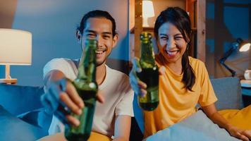 heureux jeune couple asiatique regardant la caméra profiter d'un événement de soirée en ligne assis sur un canapé appel vidéo avec des amis boire de la bière via un appel vidéo en ligne dans le salon à la maison, concept de distanciation sociale. photo