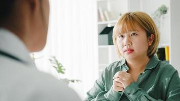 une jeune femme médecin asiatique en uniforme médical blanc utilisant un presse-papiers livre d'excellentes nouvelles discutent des résultats ou des symptômes avec une patiente assise au bureau dans une clinique de santé ou un bureau d'hôpital. photo