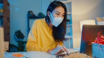 une jeune femme d'affaires asiatique porte un masque facial, vérifie le bon de commande et répond au chat de la boîte de réception du client sur un ordinateur portable au bureau à domicile la nuit. propriétaire de petite entreprise, livraison sur le marché en ligne, concept de style de vie indépendant. photo