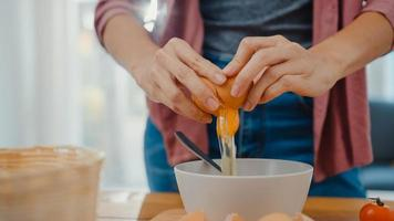 mains d'une jeune femme asiatique chef cassant des œufs dans un bol en céramique faisant cuire une omelette avec des légumes sur une planche de bois sur une table de cuisine dans la maison. mode de vie saine alimentation et concept de boulangerie traditionnelle. photo