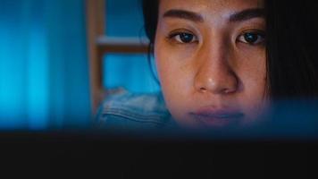 Jeune femme d'affaires chinoise millénaire travaillant tard dans la nuit avec un problème de recherche de projet sur un ordinateur portable dans le salon d'une maison moderne. concept de syndrome d'épuisement professionnel des personnes d'asie. photo