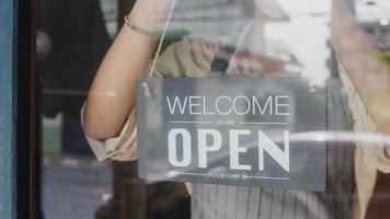 une jeune fille asiatique porte un masque facial transformant un panneau de fermé en panneau ouvert sur la porte regardant à l'extérieur en attendant les clients après le verrouillage. propriétaire petite entreprise, nourriture et boisson, concept de réouverture de l'entreprise. photo