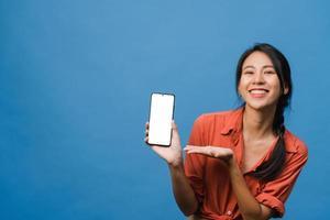 une jeune femme asiatique montre un écran de smartphone vide avec une expression positive, sourit largement, vêtue de vêtements décontractés, se sentant heureuse sur fond bleu. téléphone portable avec écran blanc en main féminine. photo