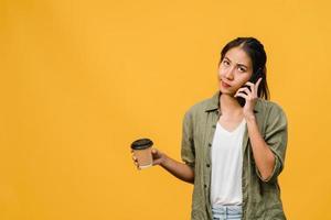 une jeune femme asiatique parle par téléphone et tient une tasse de café avec une expression négative, des cris excités, pleure émotionnellement en colère dans un tissu décontracté et se tient isolée sur fond jaune. concept d'expression faciale. photo