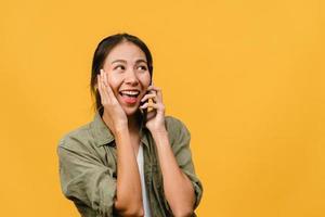 une jeune femme asiatique parle par téléphone avec une expression positive, sourit largement, vêtue de vêtements décontractés, se sentant heureuse et se tient isolée sur fond jaune. heureuse adorable femme heureuse se réjouit du succès. photo