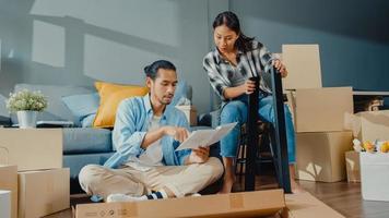 Heureux jeune couple asiatique séduisant homme et femme s'entraident pour déballer la boîte et assembler des meubles décorer une table de construction de maison avec une boîte en carton dans le salon. concept de déménagement asiatique jeune marié. photo