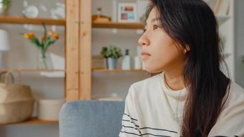 une dame asiatique réfléchie s'assoit embrassant les genoux sur un canapé dans le salon de la maison regarde à l'extérieur avec une sensation de solitude, un adolescent triste et déprimé passe du temps seul à la maison, à distance sociale, quarantaine de coronavirus. photo