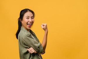 jeune femme asiatique à l'expression positive, joyeuse et excitante, vêtue d'un tissu décontracté et regarde la caméra sur fond jaune. heureuse adorable femme heureuse se réjouit du succès. concept d'expression faciale. photo