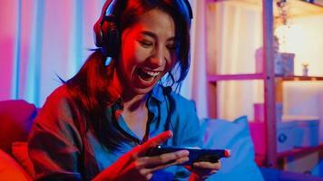 une joyeuse joueuse asiatique porte un jeu vidéo de compétition de casque en ligne avec une conversation excitée par smartphone avec un ami assis sur un canapé dans un salon aux néons colorés à la maison, concept d'activité de quarantaine à domicile. photo