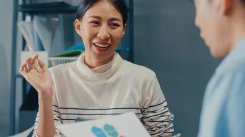 heureux jeunes hommes d'affaires et femmes d'affaires asiatiques se réunissant pour réfléchir à de nouvelles idées sur le projet à son partenaire travaillant ensemble pour planifier une stratégie de réussite profitez du travail d'équipe dans un petit bureau à domicile moderne. photo