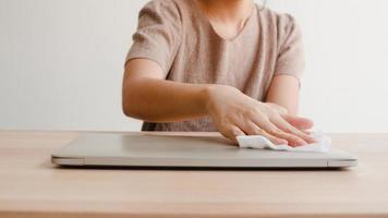 femme asiatique utilisant un spray d'alcool sur un ordinateur portable propre avant d'ouvrir pour protéger le coronavirus. ordinateur propre féminin pour l'hygiène lorsque la distanciation sociale reste à la maison et le temps d'auto-quarantaine. photo
