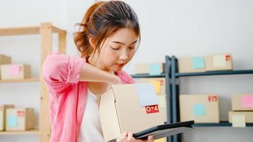 jeune femme d'affaires entrepreneur asiatique vérifier le bon de commande du produit en stock et enregistrer sur le travail de l'ordinateur tablette au bureau à domicile. propriétaire de petite entreprise, livraison sur le marché en ligne, concept de style de vie indépendant. photo