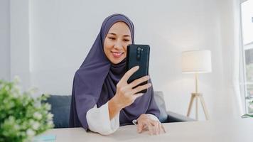 jeune femme d'affaires musulmane d'asie utilisant un téléphone intelligent pour parler à un ami par vidéoconférence remue-méninges en ligne tout en travaillant à distance depuis la maison dans le salon. distanciation sociale, quarantaine pour le virus corona. photo