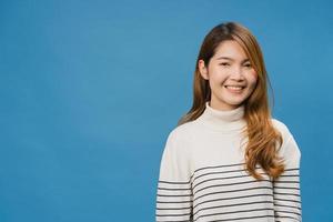 jeune femme asiatique à l'expression positive, sourire largement, vêtue de vêtements décontractés et regardant la caméra sur fond bleu. heureuse adorable femme heureuse se réjouit du succès. concept d'expression faciale. photo