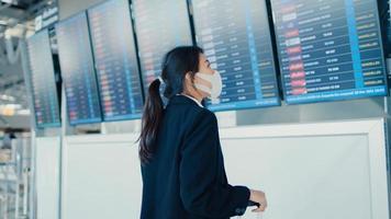 une fille d'affaires asiatique porte un masque facial avec un support de valise devant le conseil d'administration pour consulter les informations vérifiant son vol à l'aéroport international. pandémie de covid de banlieue d'affaires, concept de voyage d'affaires. photo