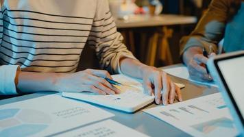 Les hommes d'affaires de l'Asie se réunissent sur les statistiques d'analyse du plan de remue-méninges et l'en-tête de l'équipe tiennent le graphique du point de la tablette et l'employé prend note dans la nuit du bureau à domicile moderne. concept de réussite de la stratégie financière. photo