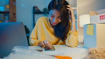 jeune femme d'affaires d'asie vérifier l'achat en ligne sentiment de paiement surprise message bancaire au bureau à domicile la nuit. propriétaire de petite entreprise, livraison sur le marché en ligne, concept de style de vie indépendant. photo
