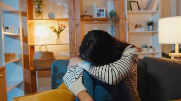 une dame asiatique réfléchie souffrant d'insomnie s'assoit sur un canapé dans le salon la nuit à la maison avec une sensation de solitude, une adolescente triste et déprimée passe du temps seule à la maison, à distance sociale, quarantaine de coronavirus. photo