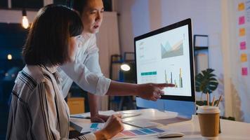 groupe d'hommes d'affaires et de femmes d'affaires asiatiques utilisant une présentation informatique et une réunion de communication pour réfléchir à des idées sur les nouveaux collègues du projet travaillant sur la stratégie de réussite du plan dans le bureau à domicile de nuit. photo