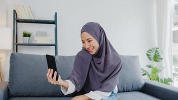 une dame musulmane d'asie porte le hijab à l'aide d'un appel vidéo téléphonique parlant avec un couple à la maison. jeune adolescent faisant une vidéo vlog sur les réseaux sociaux sur un canapé dans le salon. distanciation sociale, quarantaine pour le virus corona. photo