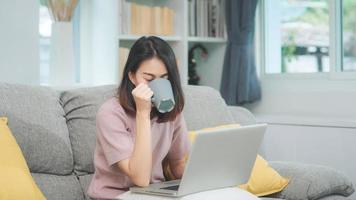 jeune femme asiatique indépendante travaillant sur un ordinateur portable vérifiant les médias sociaux et buvant du café en position allongée sur le canapé pour se détendre dans le salon à la maison. femmes de style de vie au concept de maison. photo