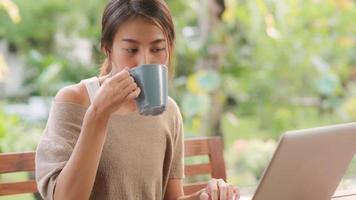 femme asiatique indépendante travaillant à la maison, femme d'affaires travaillant sur ordinateur portable et buvant du café assis sur une table dans le jardin le matin. femmes de style de vie travaillant à la maison concept. photo