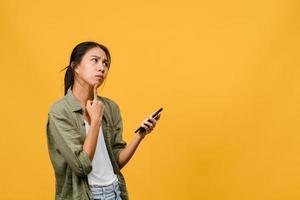 pensant rêver d'une jeune femme asiatique utilisant un téléphone avec une expression positive, vêtue d'un tissu décontracté, se sentant heureuse et se tenant isolée sur fond jaune. heureuse adorable femme heureuse se réjouit du succès. photo