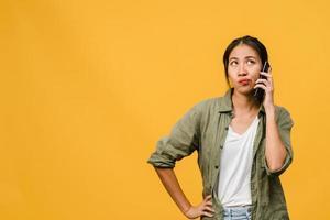 une jeune femme asiatique parle par téléphone avec une expression négative, des cris excités, des cris émotionnels en colère dans un tissu décontracté et se tient isolée sur fond jaune avec un espace de copie vierge. concept d'expression faciale. photo